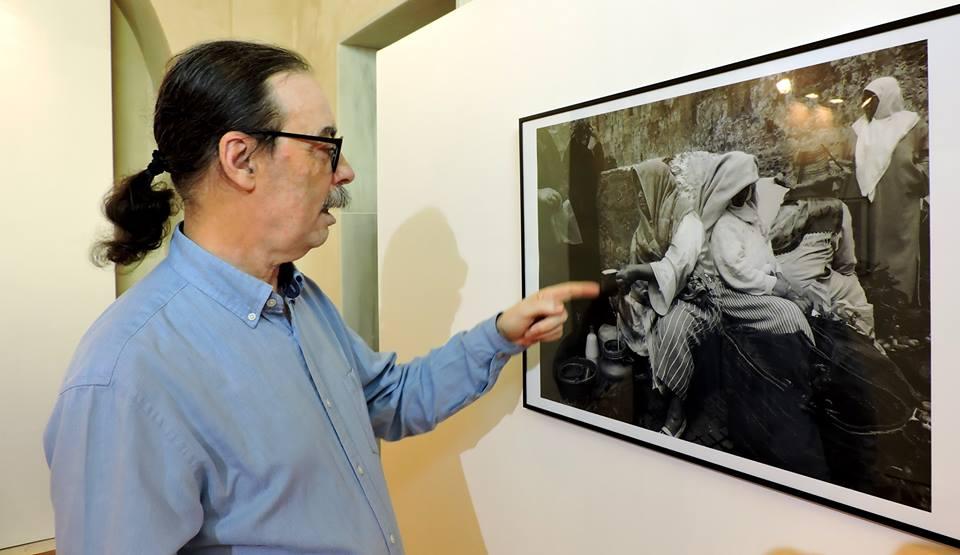 El autor señala una de las fotografías expuestas.