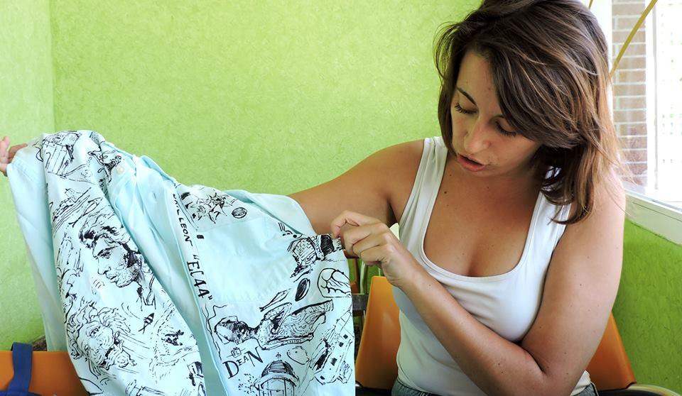 Mª Luz Reyes muestra los dibujos de la camisa original.